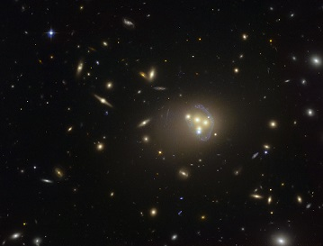 Arced streaks demonstrate gravitational lensing of light of distant galaxies [6].